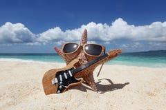 De speler van de zeestergitaar op strand Royalty-vrije Stock Afbeelding