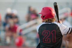 De speler van het middelbare schoolhonkbal met het lange haar slaan Stock Foto's