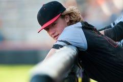 De speler van het middelbare schoolhonkbal met lang haar die op dugout moeras leunen Stock Afbeeldingen