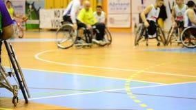De speler van het rolstoelbasketbal in een spel stock videobeelden