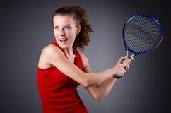 De speler van het vrouwentennis tegen donkere achtergrond Royalty-vrije Stock Foto