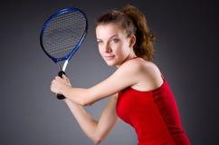 De speler van het vrouwentennis tegen donkere achtergrond Royalty-vrije Stock Afbeelding