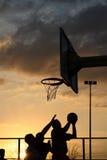De spelers van het basketbal bij de zonsondergang Royalty-vrije Stock Foto's
