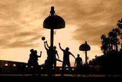 De spelers van het basketbal bij zonsondergang Royalty-vrije Stock Foto's