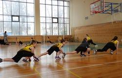 De spelers van het meisjesbasketbal warmen alvorens aan stadscompetities deel te nemen op stock afbeeldingen