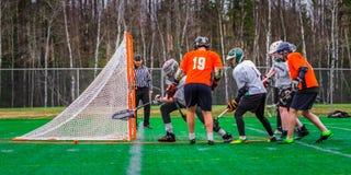 De spelers van de lacrossesport op het gebied stock afbeelding