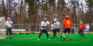 De spelers van de lacrossesport op het gebied stock foto