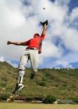 De spelersprongen van het honkbal om een vliegbal te vangen Stock Fotografie