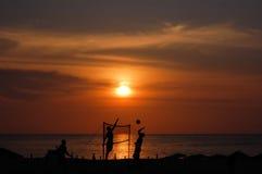 De spelerssilhouetten van het strandvolleyball bij zonsondergang Stock Foto's