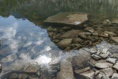 De spiegelbezinning van het bergmeer en grote grijze stenen royalty-vrije stock afbeeldingen