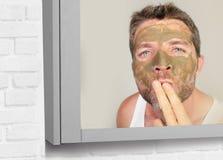 De spiegelportret van de levensstijlbadkamers van de jonge aantrekkelijke gelukkige mens met groene room op zijn gezicht die gezi stock afbeeldingen