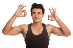 De spier Aziatische mens toont o.k. met ei Royalty-vrije Stock Foto