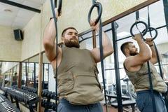 De spier Kaukasische gebaarde mens die oefeningen doen kleedde zich in gewogen vest in de gymnastiek, militaire stijl stock foto's