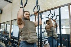 De spier Kaukasische gebaarde mens die oefeningen doen kleedde zich in gewogen vest in de gymnastiek, militaire stijl royalty-vrije stock foto