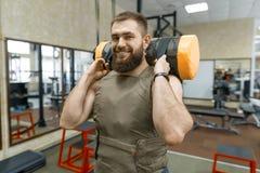 De spier Kaukasische gebaarde mens die oefeningen doen kleedde zich in gewogen vest in de gymnastiek, militaire stijl royalty-vrije stock fotografie