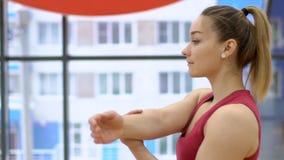 De spieren van de vrouwenrek van één hand vóór fysieke inspanning in gymnastiek stock footage