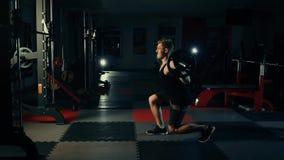 De spiermens in de gymnastiek die zijn benen opleiden quadriceps en verlamt met een concept van het barruilmiddel geschiktheid en stock video
