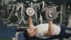 De spiermens in de gymnastiek heft gewichten op die op een bank liggen stock video