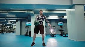 De spiermens heft zware kettlebell boven zijn hoofd in heldere gymnastiek in langzame motie op stock video