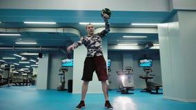 De spiermens heft zware kettlebell boven zijn hoofd in heldere gymnastiek in langzame motie op stock footage