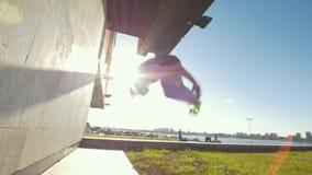 De spiermens voert tik uit weg duwend van de muur bij zonnige dag stock videobeelden