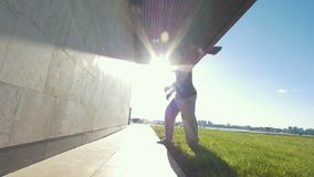 De spiermens voert tik uit weg duwend van de muur bij zonnige dag stock video