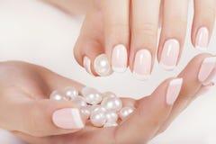 De spijkers van de mooie vrouw met Franse manicure Stock Afbeeldingen