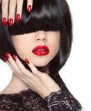 De Spijkers van Manicured Rode Lippen Zwart loodjeskapsel Donkerbruin meisje in leerjasje Stock Afbeeldingen
