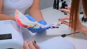 De spijkertechnicus toont het kleurenpalet van de spijkerdiensten in schoonheidssalon Royalty-vrije Stock Foto's