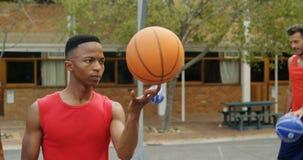 De spinnende bal van de basketbalspeler op vinger stock video