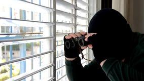 De spion in balaclava masker kijkt door de blindzonneblinden stock video