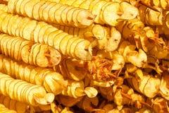 De spiraalvormige aardappels braadden, op houten stokken, spiraal Verkopend voedsel bij de markt Ongezond gebraden voedsel Straat royalty-vrije stock foto's