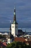 De spits van Oleviste-Kerk onder een donkere bewolkte hemel Oud Tallinn Stock Foto's