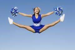 De Spleten van Cheerleaderwith pompoms doing tegen Hemel Royalty-vrije Stock Afbeelding
