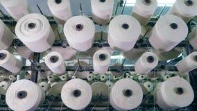 De spoelen met draden roteren op een rek bij een textielinstallatie industriële stoffenproductielijn stock videobeelden