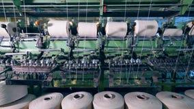 De spoelen met witte draden worden mechanisch afgewikkeld De productiemateriaal van de kledingstukfabriek stock videobeelden