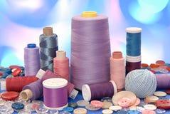 De spoelen van draad en de knopen zijn op artistieke veelkleurige backg stock afbeelding