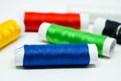 De spoelen van kleurrijke draad concentreerden zich op blauwe spoel Stock Foto's