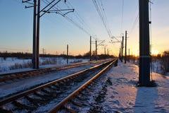 De spoorweg in de stralen van zonsondergang stock foto