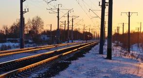 De spoorweg in de stralen van zonsondergang stock foto's