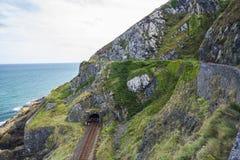 De spoorweg door steen schommelt berg bij Ierse zeekust stock foto's