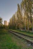 De spoorweg gaat naar de heldere high-rise bouw Stock Afbeelding