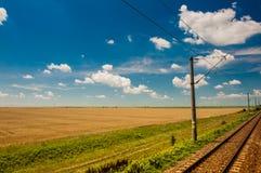 De spoorweg gaat naar horizon in groen en geel landschap onder blauwe hemel met witte wolken Royalty-vrije Stock Foto