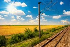 De spoorweg gaat naar horizon in groen en geel landschap onder blauwe hemel met witte wolken Stock Foto's