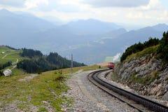 De spoorweg met een trein met mening over de bergen en een meer in de wolken Royalty-vrije Stock Afbeelding