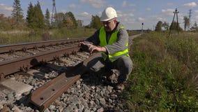 De spoorwegarbeider neemt beelden van de sporen stock video