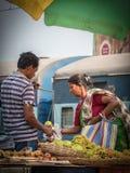 De spoorwegverkoper verkoopt vruchten aan de reizigers stock afbeeldingen