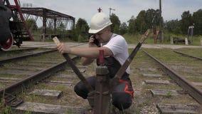 De spoorwegwerknemer spreekt telefonisch bij de schakelaars stock video