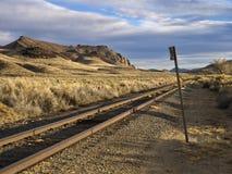 De sporen die van de spoorweg de woestijn doornemen stock foto's