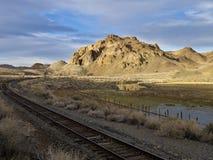 De sporen die van de spoorweg voorbij een woestijnboerderij lopen royalty-vrije stock fotografie